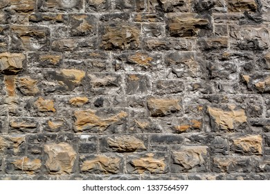 Closeup of a weathered rough textured industry stone brick  wall outdoors.