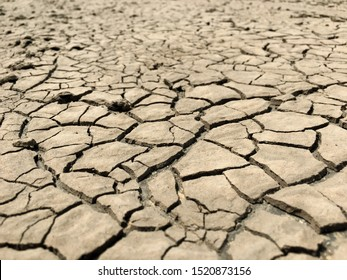 Closeup weathered texture and background of arid cracked ground. Broken dried mud from arid problem. Global warming crisis. Agricultural land without water. Climate change