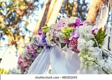 Closeup wedding arch decorated with beautiful floral bouquets. Floral compositions with fresh roses, asters and fern leaves.