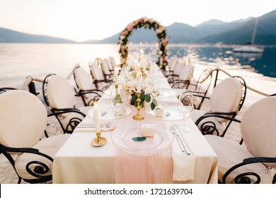 Close-up of a wedding dinner table reception. A table stands on beach overlooking mountains at sunset. Metal forged chairs, burning candles, wedding arch of flowers, cream-colored cloth tablecloth.