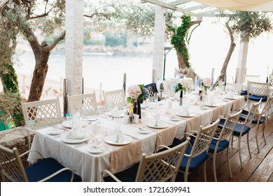Close-up of a wedding dinner table at reception. A long table with metal chairs with blue pillows, in a stone gazebo between olive trees, overlooking Sveti Stefan Island, in Montenegro.