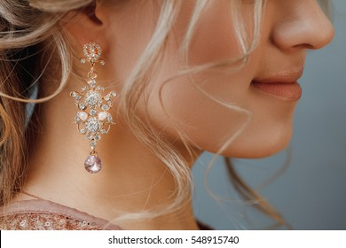 Closeup of wedding hairstyle with jewerly earrings pearls of bride