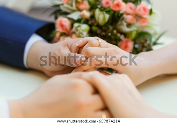Close-up of wedding hands with rings and bouquet lie on the table