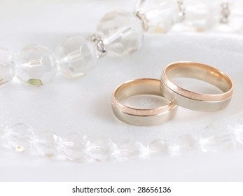 Closeup of wedding rings and beads on a veil