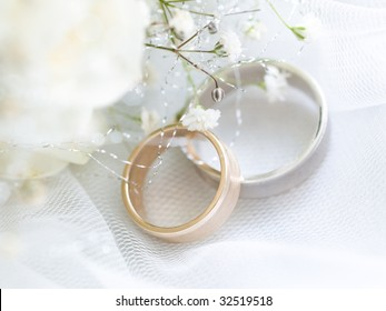 Closeup of wedding rings with flowers