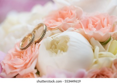 Close-up of wedding rings on background of roses & peonies
