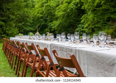 Closeup of wedding table decorated by flowers in the garden in nature.