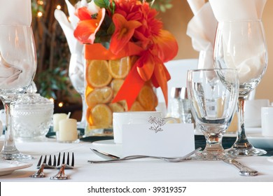 Closeup of a wedding table place setting with colorful centerpiece made up of sliced oranges in a vase.