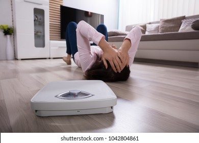 Close-up Of A Weighing Scale Besides Woman Lying On Hardwood Floor