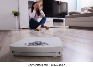 Close-up Of A Weighing Scale In Front Of Upset Woman