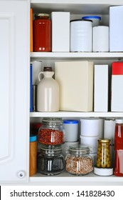 Closeup of a well stocked pantry. One door of the cabinet is open revealing canned goods, condiments, package foodstuffs, and storage jars.