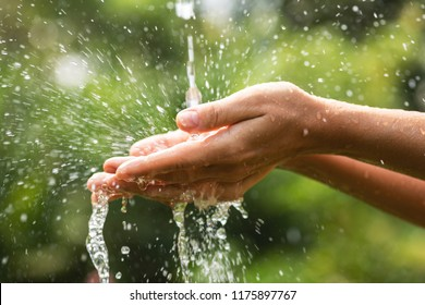 Close-up of wet female hands and clear water splashes