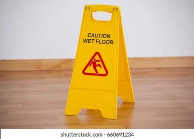 Close-up of wet floor caution sign on wooden floor