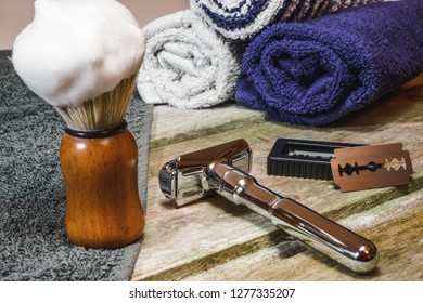 Close-up of wet shaving supplies. Shiny safety razor, lathered shaving brush, double-edge blade and barber towels.