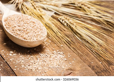 Close-up of wheat bran in wooden spoon with wheat ears. Dietary supplement to improve digestion. Source of dietary fiber. Wooden planks background. Shallow depth of field