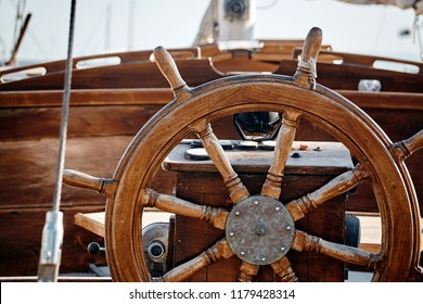 Closeup of a wheel and deck of a wooden antique sailing yacht.