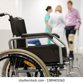 Closeup of wheelchair against patient and doctors at hospital