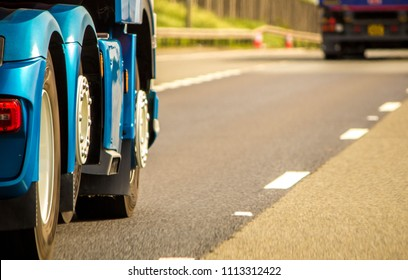 A closeup of wheels in motion from an articulated lorry, travelling along a UK motorway.
