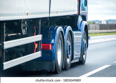 A closeup of wheels in motion from an articulated lorry, traveling along a UK motorway.