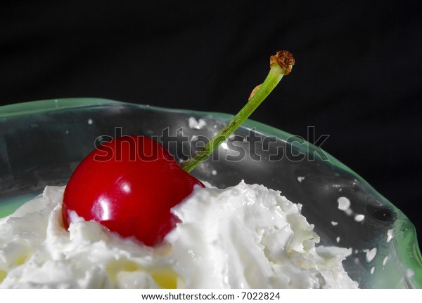 Closeup of whipped cream and a cherry in a clear glass bowl.