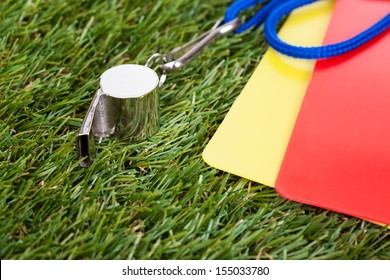 Close-up Of Whistle With Red And Yellow Card On The Field
