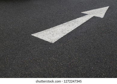Closeup of white arrow on asphalt ground of the parking lot after raining. The traffic sign show the symbol of safty and right direction to the goal.