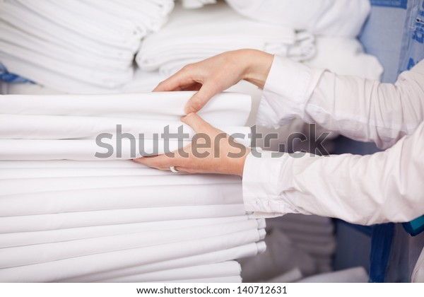 Nahaufnahme weißer Bettwäsche, die im Hotelzimmer stapelt sind