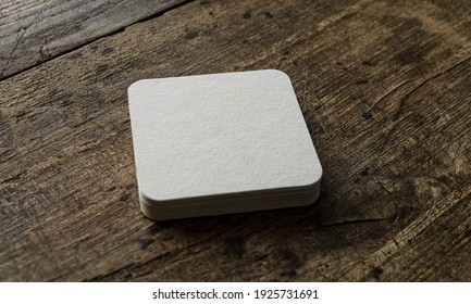 Closeup of white blank coaster on wooden background, Blank square coasters