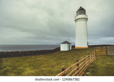 Close-up white Campbeltown lighthouse. Northern Ireland. The cloudy rainy sky background. The lonely lighthouse on the Irish shore. Epic ocean view. Stunning autumn landscape.