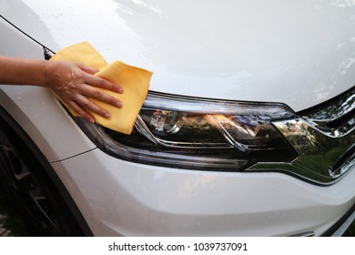 Closeup of white car cleaning  with yellow microfiber cloth by woman's hand.