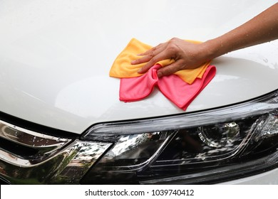 Closeup of white car cleaning  with yellow and pink microfiber cloths by woman's hand.