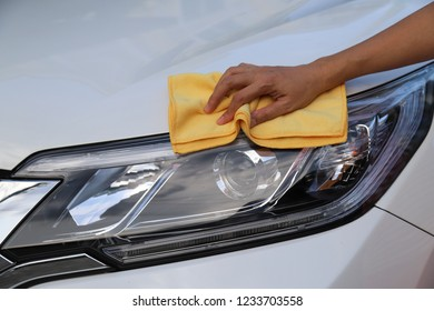 Closeup of white car cleaning  with yellow microfiber cloth by woman's hand in sunny day.