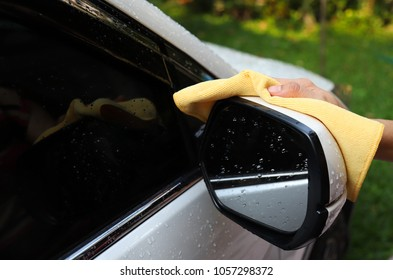 Closeup of white car washing and cleaning at right rearview mirror with yellow microfiber cloth by woman's hand in sunny day. A simple work of modern family member.