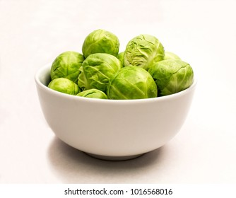 Closeup of a White Ceramic Bowl of Fresh Green Brussels Sprouts on a white background