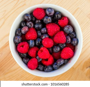 Closeup of a White Ceramic Bowl Full of Bluberries and Red Raspberries