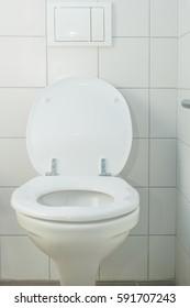 closeup of white ceramic toilets in a bathroom