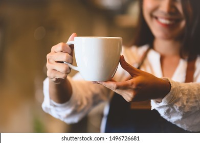 Closeup of white coffee cup with beautiful Asian woman barista background for serving to customer. Job and occupation. Food and drink beverage. Coffee shop and Cafe. Business and restaurant ownership