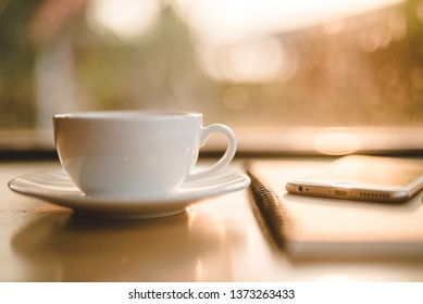 Close-up white coffee cup on wood table near window with light shade on tabletop at cafe. - Image