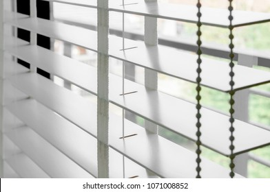 Closeup white color wooden blind with white ladder tape curtains.Sunlight through the windows in the city with garden.Selective focus and light image backdrop.