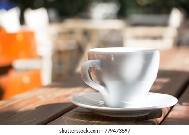 A closeup of a white cup of coffee with a plate on a wooden table outdoors, sun light.