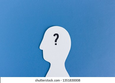 Closeup of white cutout of anonymous man with question mark in brain on blue background