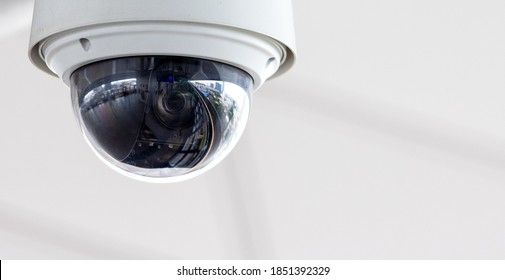 Closeup of white dome type cctv digital security camera installed on ceiling for observation.