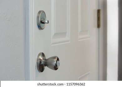 Closeup of a white door with lock and deadbolt, safety security insurance protection concept, vertical shot, copy white text space, angled view