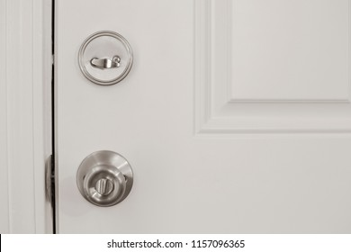Closeup of a white door with lock and deadbolt, safety security insurance protection concept, vertical shot, copy white text space, straight forward head on view