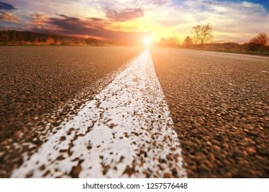 Close-up of a white driving line on an empty asphalt road with a forest and night sky with sunset on the background