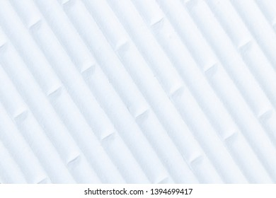 Close-up of white flip flop rubber sole profile with abstract pattern of diagonal lines and alternating lines. High key exposure.