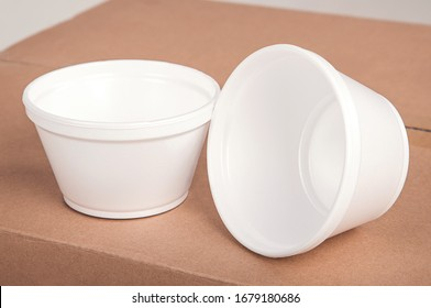 Closeup white foam cups stand on a cardboard box on an isolated background.