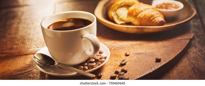 Close-up of a white full coffee cup served as breakfast on a vintage wooden tray next to a delicious French croissant filled with vanilla cream