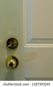 Close-up of a white interior door showing a brass door knob and deadbolt lock
