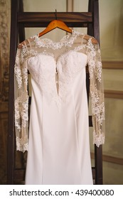 closeup of white lace and silk wedding dress on vintage stairs during bride's preparation